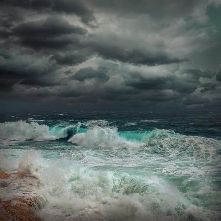 Vista al mar tormentoso cerca de la costa al atardecer. Olas, gotas salpicadas bajo un cielo dramático oscuro. Foto de archivo