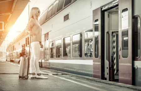 Blonde woman with her luggage stay near the red train on the peron os rail station under sun light at sunny day. Reklamní fotografie