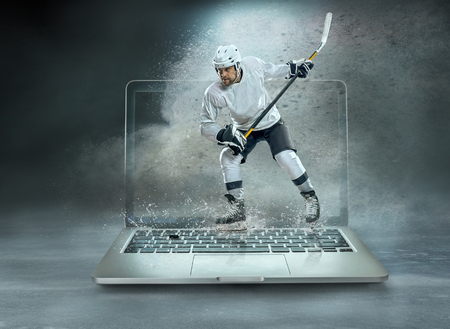 Caucassian ice hockey Players in dynamic action in a professional sport game play on the laptop in hockey under stadium lights. Stock Photo - 120991758