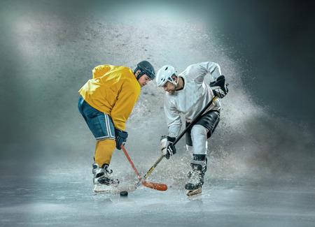 Joueurs de hockey sur glace caucassiens en action dynamique dans un jeu de sport professionnel jouent sur l'ordinateur portable au hockey sous les lumières du stade.