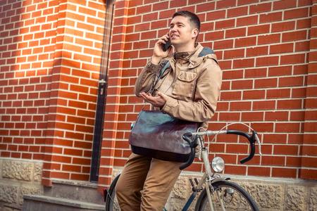 Young stylish businessman with his smartphone in hand stay near red wall with sport retro bike in sunny day.