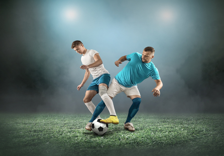 Soccer player on a football field in dynamic action at summer day under sky with clouds. Sporty man is shooting the ball outdoor. Imagens