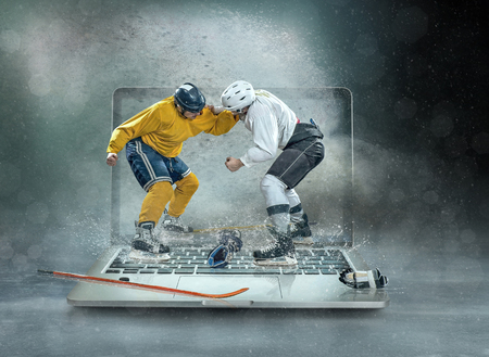 Caucassian Eishockey Spieler in dynamischer Aktion in einem professionellen Sportspiel spielen auf dem Laptop im Eishockey unter Stadionbeleuchtung. Standard-Bild