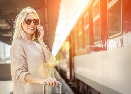 Blonde woman with her luggage stay  and speak in her mobile near the red train on the peron os rail station under sun light at sunny day.