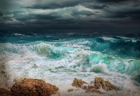 Stormachtig uitzicht op zee in de buurt van kustlijn op moment van de avond. Golven, bespat druppels onder donkere dramatische hemel.