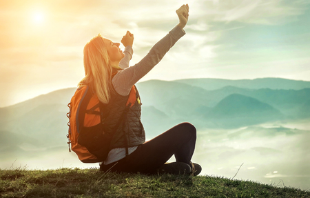 Happy woman tourist sitting on the green grass on the peak of mountain and look on the nice fog view. Concept freedom. Imagens