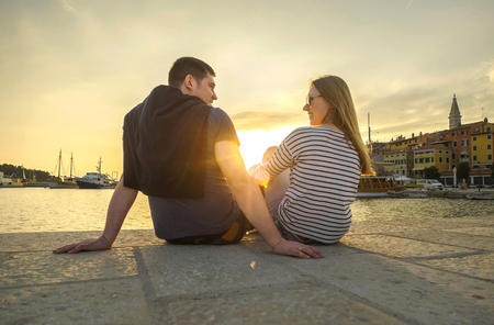 Happy couple of lovers relaxing on the sea pier