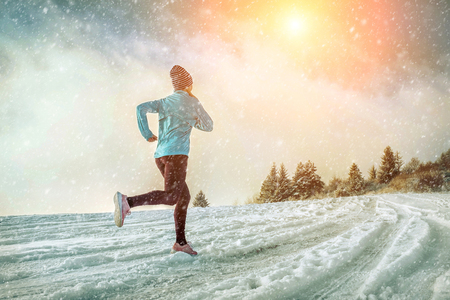 Running woman. Runner on the snow in winter sunny day. Female fitness training outdoors. Stockfoto