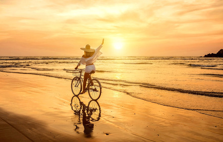Happiness woman traveler with her bicycle rides on sea coastline and looking on beautifull sunset sky in sunny summer day on beach. Freedom, Travell, Journej,  concept. Stock fotó