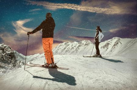 Uomini e donna sullo sci prima dell'azione sportiva al giorno soleggiato intorno alle montagne sotto cielo blu. Archivio Fotografico