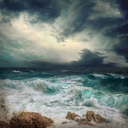 Stürmischer Meerblick in der Nähe der Küste zur Abendzeit. Wellen, spritzte Tropfen unter dunklem dramatischem Himmel.