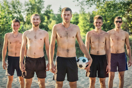 Group of Happy beach soccer players stay with ball after football game on the sand under sun light in summer time and in sunny day. Soccer on the sand.