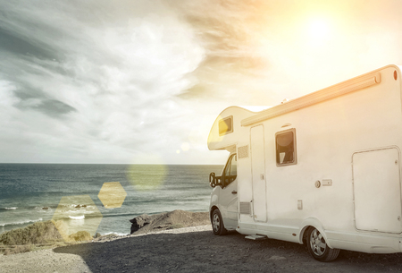 White travel caravan car stay on the beautifull ocean coastline with natural view in sunny day. Freedom, Family, Travell, Journej, Travelers concept. Stock Photo