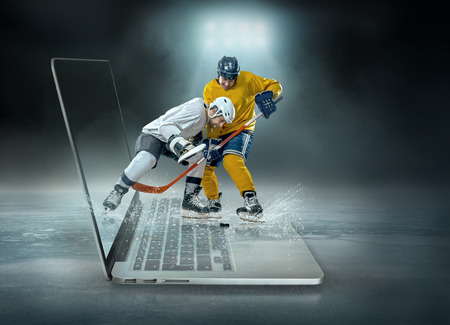 Caucassian ice hockey Players in dynamic action in a professional sport game play on the laptop in hockey under stadium lights. 스톡 콘텐츠