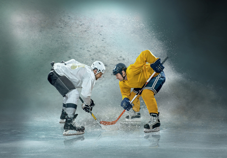 Caucassian ice hockey Players in dynamic action in a professional sport game play on the laptop in hockey under stadium lights. Stock Photo - 123219069