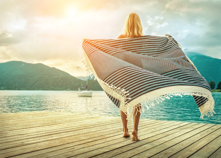 Happiness blonde woman stay on the wooden pier near the mountain lake under sunlight in morning time in summer.