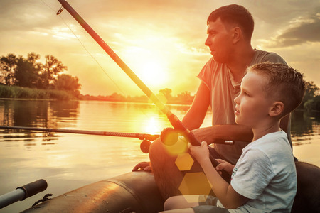 Happy Father and Son together fishing from a boat at sunset time in summer day under beautiful sky on the lake.