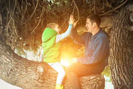 Happy childhood, father and son sit on a tree on a sunny day, family vacations