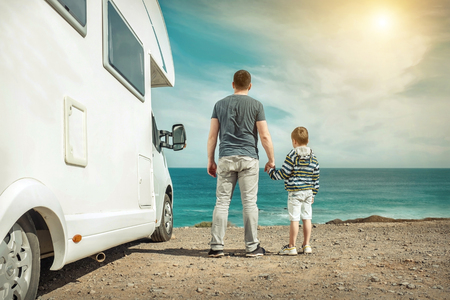 Happiness father and son, stay near them white travel car and look on the beautifull ocean coastline view in sunny day. Freedom, Family, Travell, Journej, Togetherness concept.