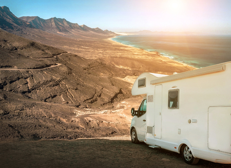 White travel caravan car stay on the beautifull ocean coastline with natural view in sunny day. Freedom, Family, Travell, Journej, Travelers concept. Reklamní fotografie