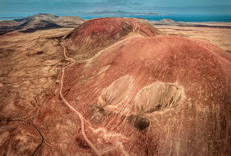 Beautiful panoramic birds eye view on Calderon Hondo, Fuerteventura island. Aerial shooting vulcano around mountains with ocean coastline at sunny day. Travell, Mountains,islands, nature, freedom concept.