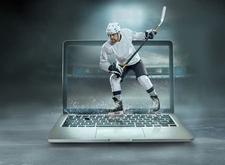 Caucassian ice hockey Players in dynamic action in a professional sport game play on the laptop in hockey under stadium lights. Stock Photo