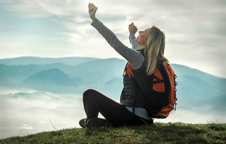 Happy woman tourist sitting on the green grass on the peak of mountain and look on the nice fog view. Concept freedom. Reklamní fotografie