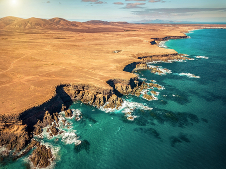 Beautiful aerial panoramic view on the ocean coastline near mountains at sunny day on Fuerteventure island. Travell, jorney,islands, nature, freedom concept.