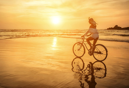 Happiness woman traveler with her bicycle rides on sea coastline and looking on beautifull sunset sky in sunny summer day on beach. Freedom, Travell, Journej,  concept. Stockfoto
