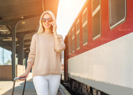 Blonde woman with her luggage go and speak in her mobile near the red train on the peron os rail station under sun light at sunny day.