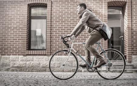 Young stylish businessmango to work on his sport retro bike in sunny day. Reklamní fotografie