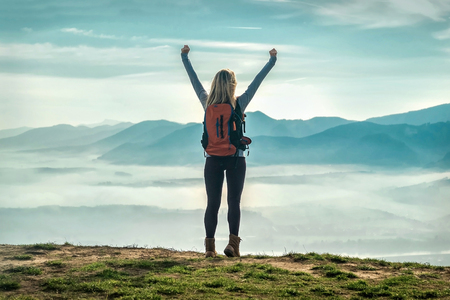 Happy woman tourist stay with open hands up on the green grass on the peak of mountain and look on the nice fog view. Concept freedom. Reklamní fotografie