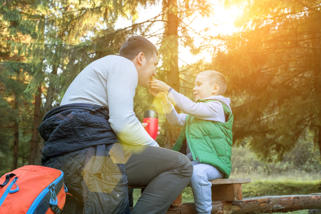 Happy father and son hikers traveler siting in wood around mountains under sunlight. Family picnic and eating food in sunny day. Holidays, vacation, travel, journey concept.
