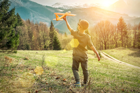 Young aviator boy with him airplane toy starting fly. Beautiful spreeng mountains view at sunny day. Travell, jorney, Aviation, Flying, freedom, holidays concept.