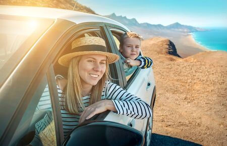 Happiness mother and son, sitting in white car and look ing on the beautiful ocean coastline with mountains. Traveler, Travel, Freedom concept. Banco de Imagens - 134582453