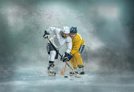 Hockey sobre hielo del Cáucaso Los jugadores en acción dinámica en un juego deportivo profesional juegan en la computadora portátil en hockey bajo las luces del estadio.