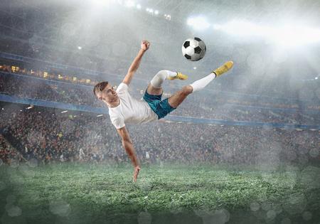 Joueur de football sur un terrain de football en action dynamique au jour d'été sous le ciel avec des nuages. Un homme sportif tire le ballon en plein air.