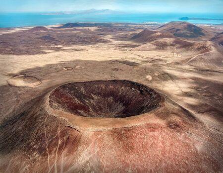 Hermosa vista panorámica de pájaro en Calderón Hondo, isla de Fuerteventura. Vulcano de tiro aéreo alrededor de las montañas con la costa del océano en un día soleado. Travell, montañas, islas, naturaleza, concepto de libertad.
