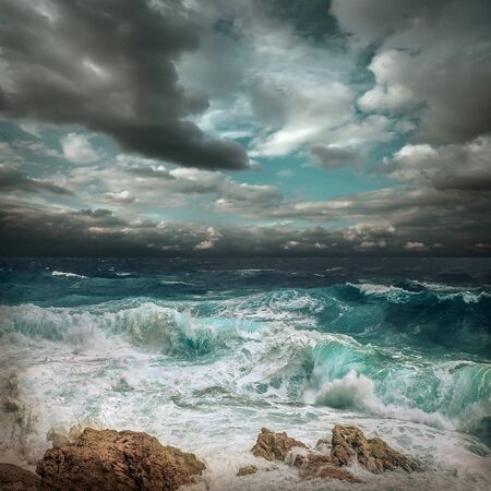 Stormy sea view  near coastline at evening time. Waves, splashed drops under dark dramatic sky.