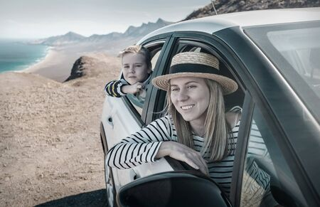 Happiness mother and son, sitting in white car and look ing on the beautiful ocean coastline with mountains. Traveler, Travel, Freedom concept. Banco de Imagens - 134582457
