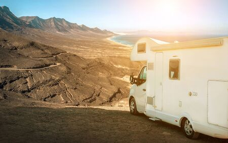 White travel caravan car stay on the beautifull ocean coastline with natural view in sunny day. Freedom, Family, Travell, Journej, Travelers concept. 版權商用圖片