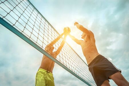 Beach Volleyball players in sunglasses in action with ball under sunlight. Popular Dynamic outdoor sport for people. Standard-Bild