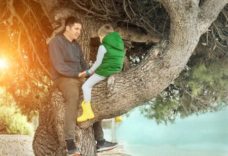 Happy childhood Bonding, father and son sitting on tree in sunny day, family holidays vacations