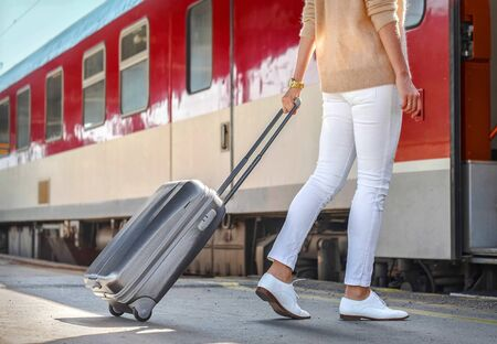 Woman with her luggage go near the red train on the peron os rail station under sun light at sunny day.