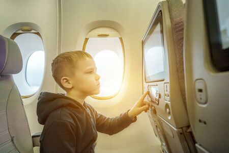 Adorable little boy traveling by airplane. Child sitting by aircraft window and looking on monitor. Traveling abroad with kids.