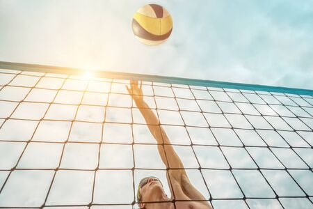 Beach Volleyball player in sunglasses in action with ball under sunlight. Popular Dynamic outdoor sport for people.