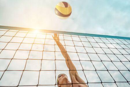 Beachvolleyballspieler mit Sonnenbrille in Aktion mit Ball unter Sonnenlicht. Beliebter dynamischer Outdoor-Sport für Menschen.