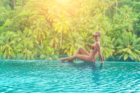 Happiness woman traveler in bikini in water pool near sea coastline  looking on beautifull tropical landscape view in sunny summer day. Freedom, Travell, Journej,  concept. Фото со стока