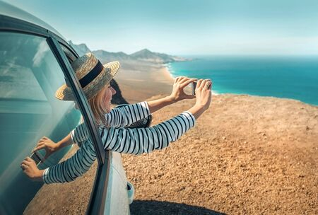 Happiness young woman traveler sitting in white car and shoot with her phone camera beautifull ocean coastline view. Freedom, Travel, Journey, Trip, Shooting concept.