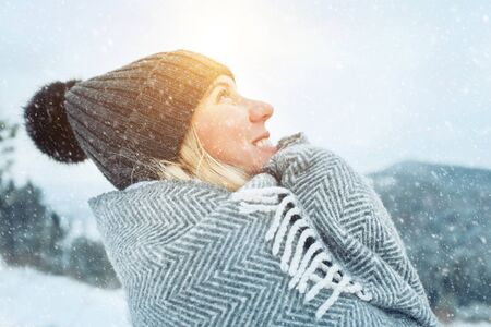Portrait Happy woman traveler on the top of mountain and looking on beautiful winter snowy view. Stock Photo